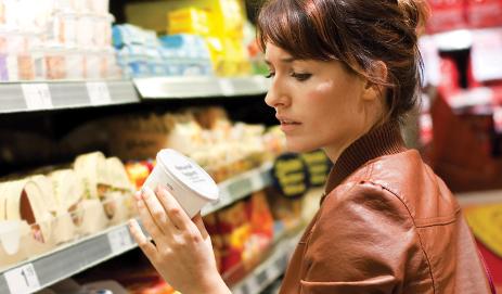 Vrouw in supermarkt die etiket bekijkt