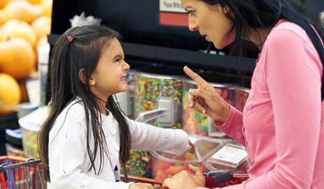 Kind die in de supermarkt jengelt voor snoep.