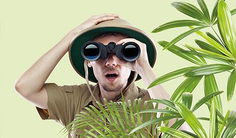 Man met verrekijker in de jungle