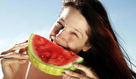 vrouw neemt hap uit meloen