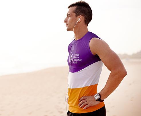 Man met hardloopshirt van het WKOF aan op het strand