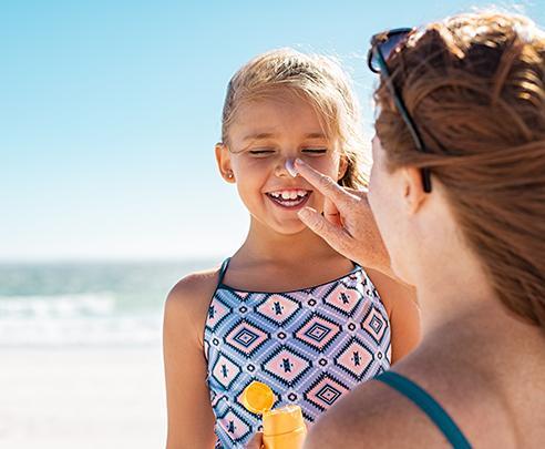 Moeder smeert zonnebrandcreme op gezicht van dochter